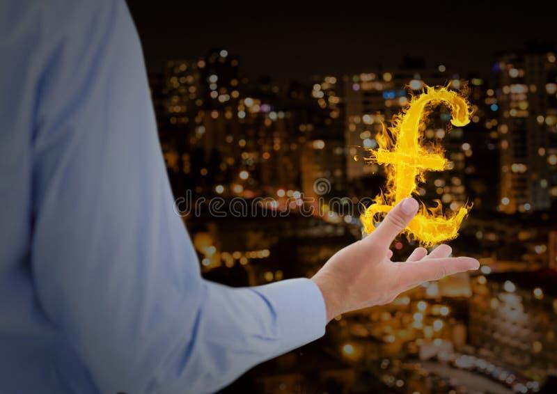 handen med pund avfyrar symbolen över framme av staden på natten royaltyfria bilder