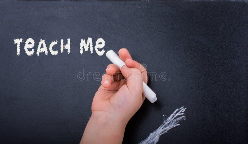 Handen med vit krita och det svarta brädet med undervisar mig etiketten royaltyfri bild