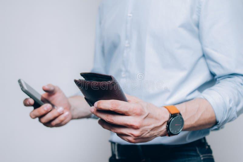 Handen met bruine portefeuille en smartphone stock afbeeldingen