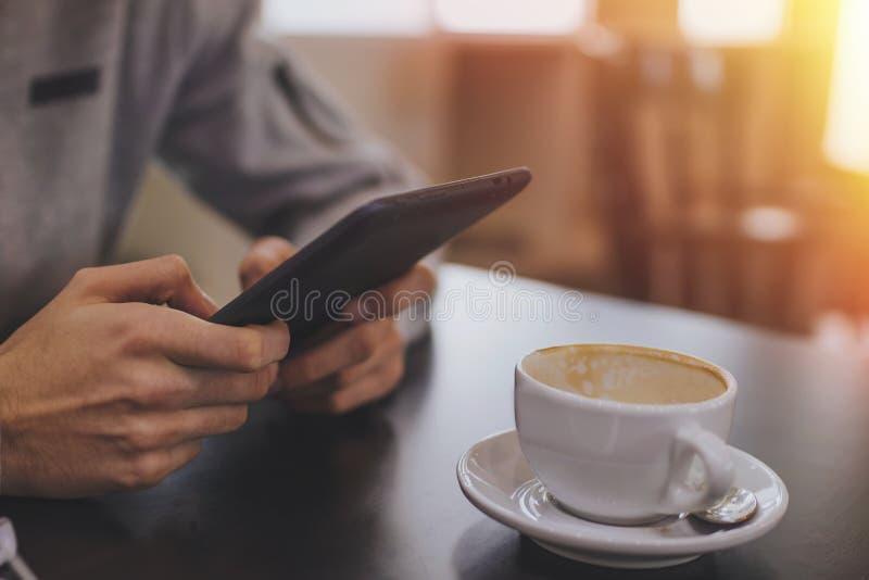 Handen met de tablet of ebook en de koffie stock fotografie
