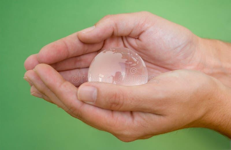 Handen met glasbol stock afbeeldingen