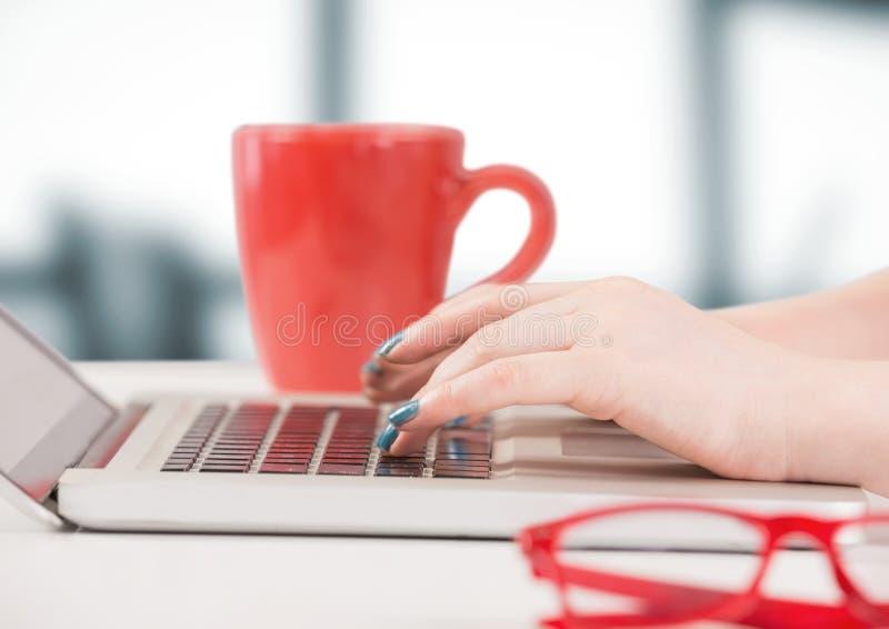 Handen met laptop en rode koffiekop tegen onscherp grijs bureau stock afbeelding