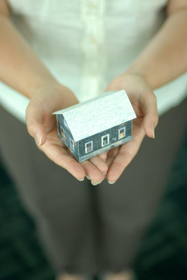Handen met model van huis. stock afbeeldingen