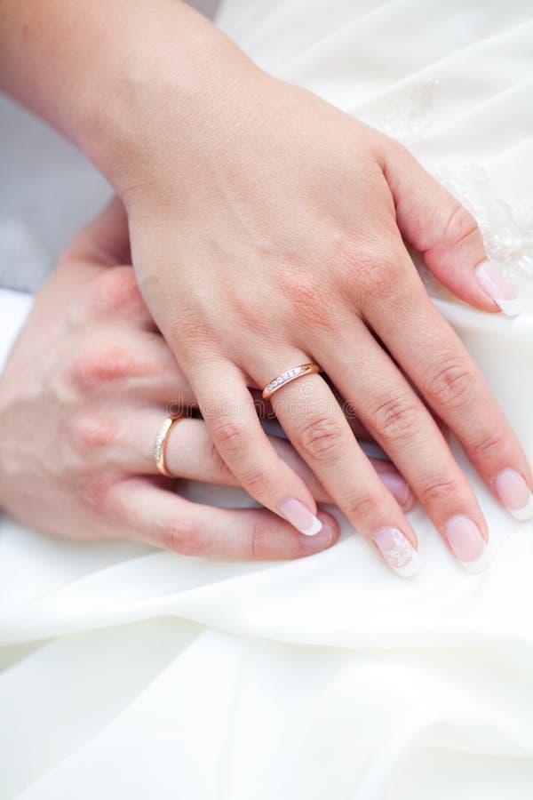 Handen met ringen van een huwelijkspaar stock afbeeldingen