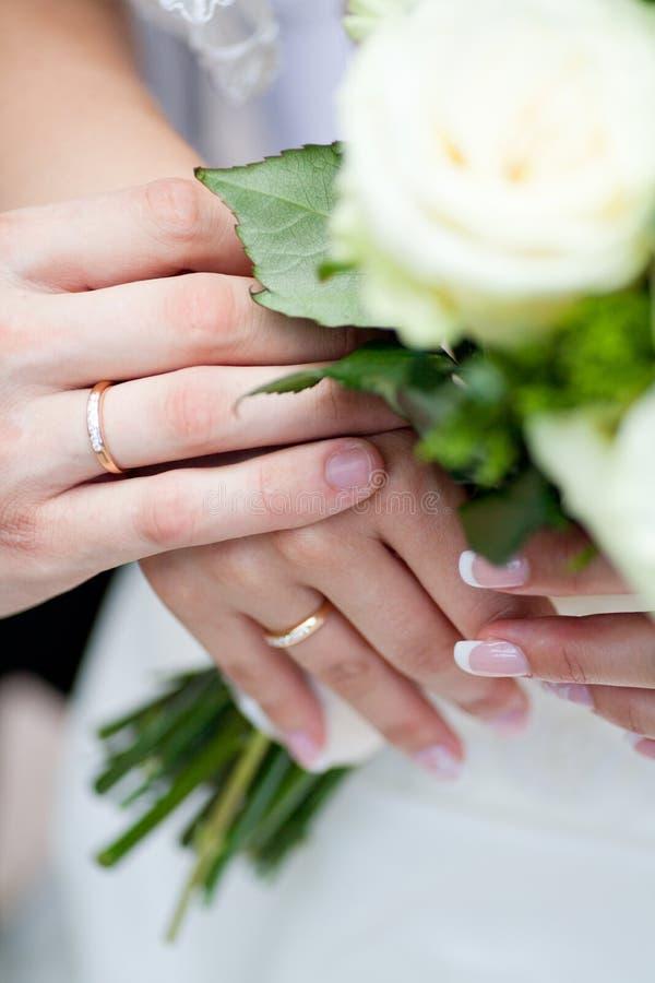 Handen met ringen van een huwelijkspaar stock afbeelding