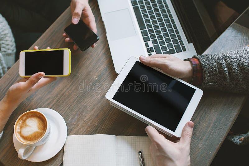 Handen met smartphones, tablet over lijst met laptop en koffie royalty-vrije stock foto's