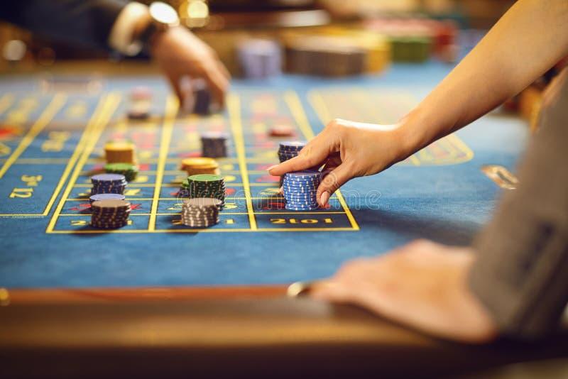 Handen met spaanders bij de lijst die van de pookroulette in een casino gokken stock foto's