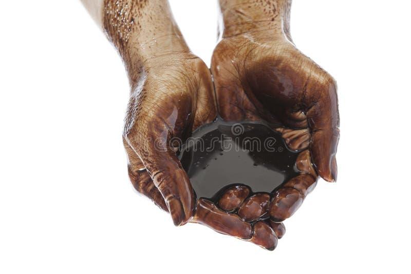 Handen met zwarte olie tot een kom die worden gevormd die stock foto