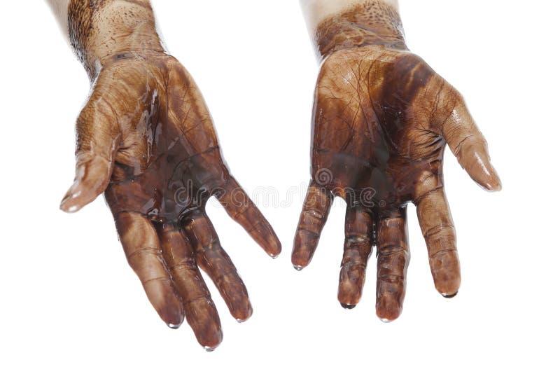 Handen met zwarte olie worden bevlekt die stock foto's