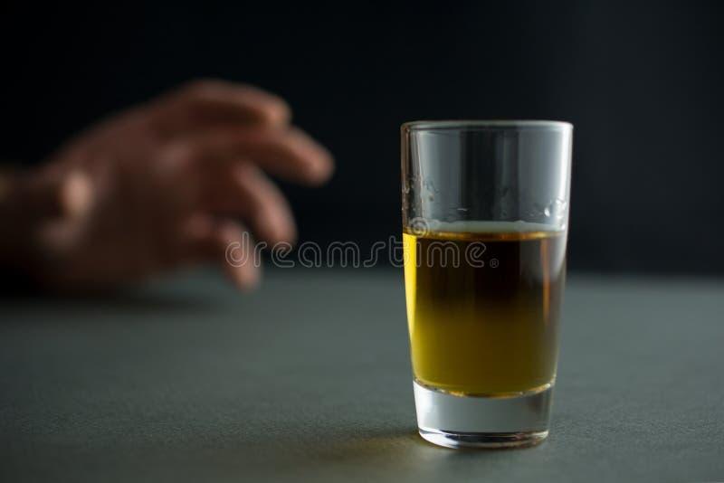 Handen når för ett exponeringsglas av whisky- eller konjak- eller alkoholdrinken royaltyfria bilder
