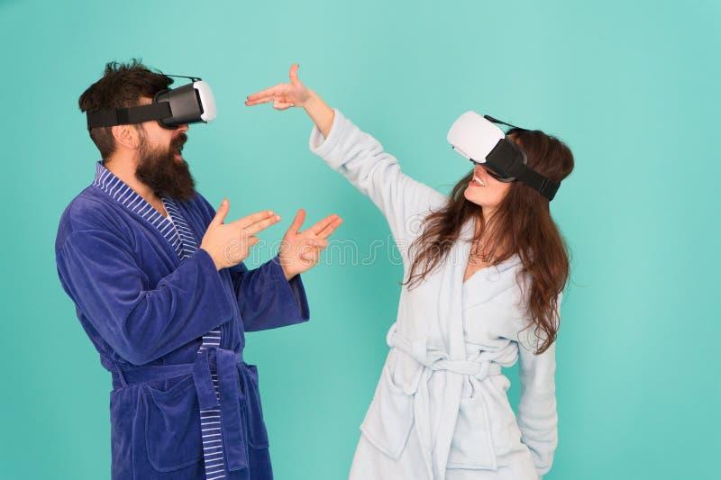 Handen omhoog De tribune en levert VR technologie en toekomst VR mededeling Opwindende indrukken Paar in badjassenslijtage royalty-vrije stock fotografie