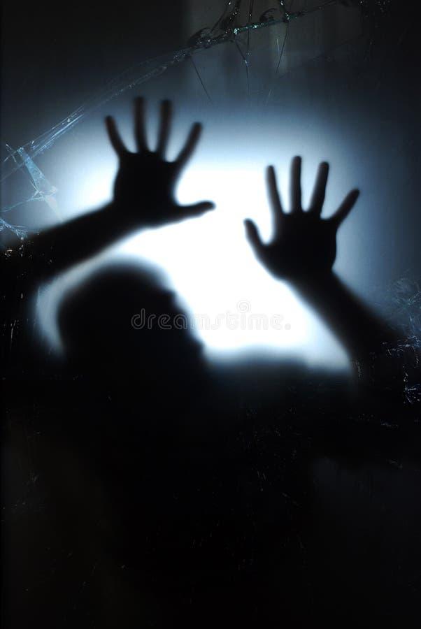 Handen op een blauw gebroken venster stock afbeeldingen