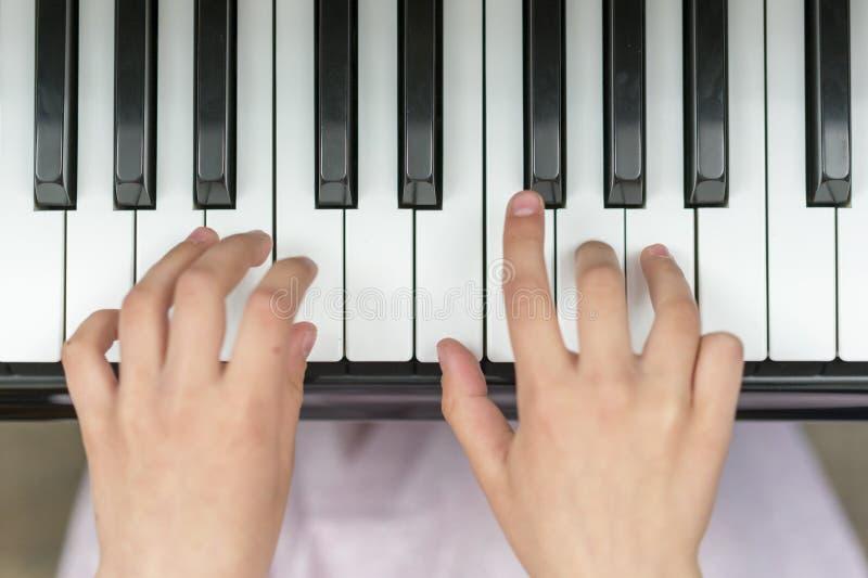 Handen op het close-up van pianosleutels De hand van het close-upmeisje het spelen piano Favoriete klassieke muziek Hoogste menin royalty-vrije stock afbeeldingen