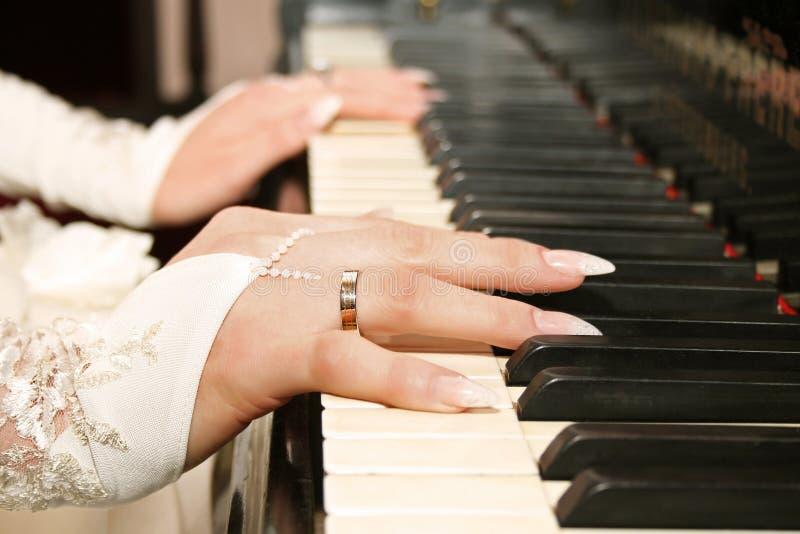 Handen op pianosleutels stock fotografie