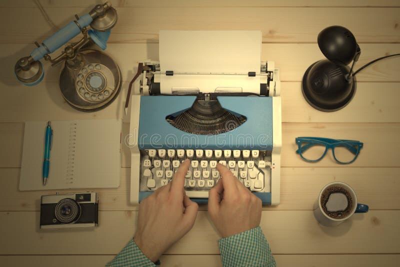 Handen op schrijfmachine bij het bureau Vlak leg stock foto's
