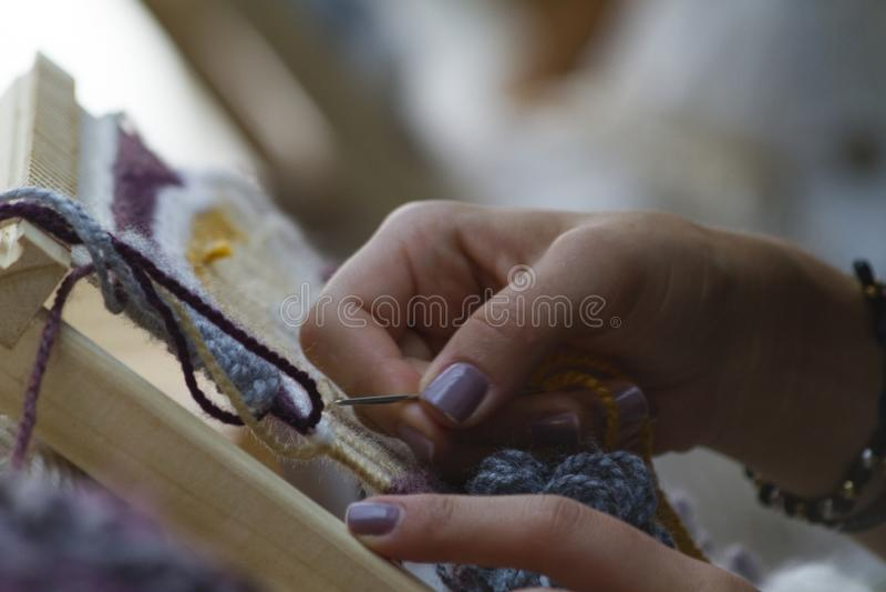 Handen op Verticaal tapijtwerkclose-up met beige draad stock foto's