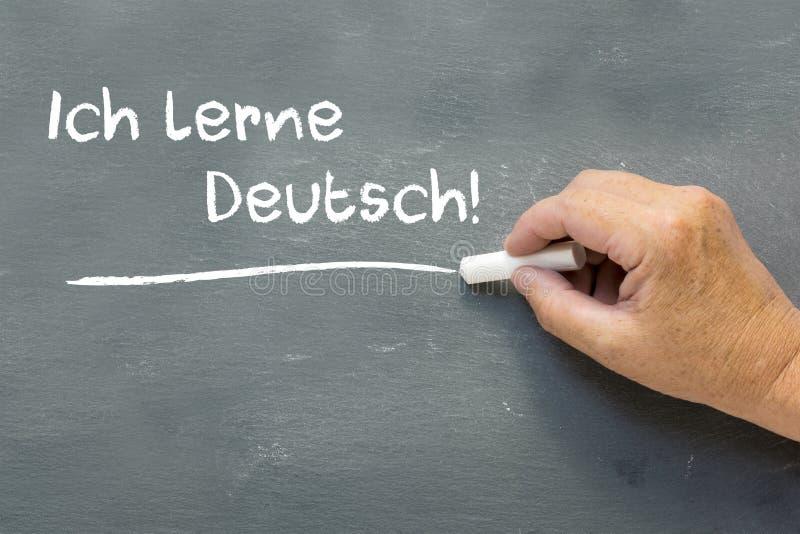 Handen på en svart tavla med tysken uttrycker Ich lerne Deutsch (I arkivfoton