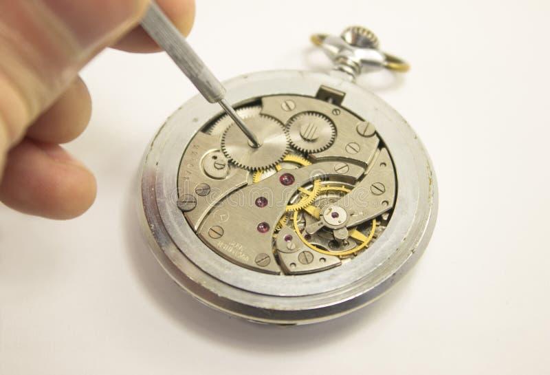 Handen reparerar den mekaniska klockan isolerat royaltyfri bild