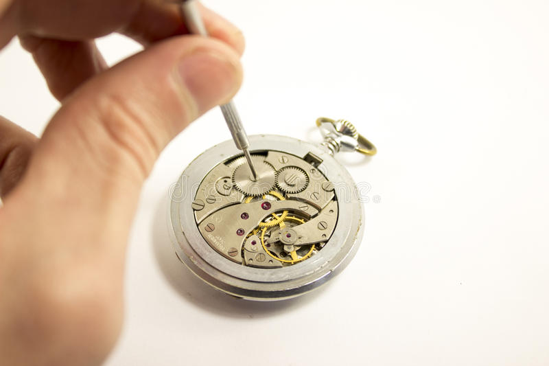 Handen reparerar en gammal klocka royaltyfri bild