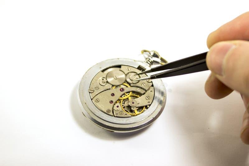 Handen reparerar en gammal mekanisk klocka royaltyfri bild