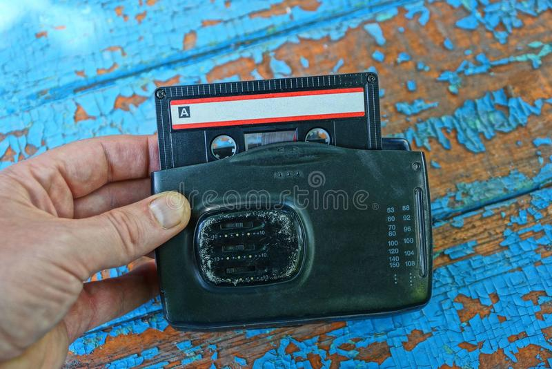 Handen rymmer den gamla svarta ljudsignal spelaren med kassetten royaltyfria bilder