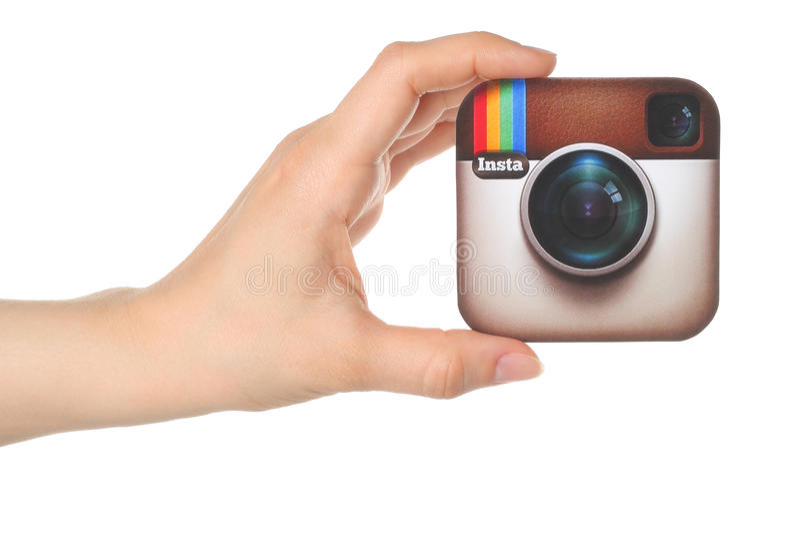 Handen rymmer den Instagram logoen utskrivaven på papper på vit bakgrund royaltyfri fotografi