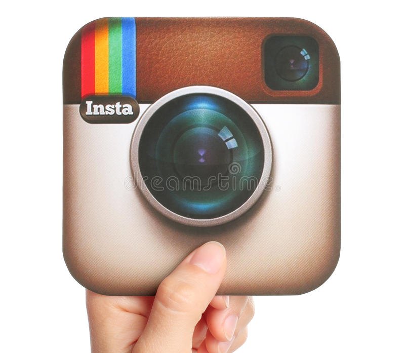 Handen rymmer den Instagram logotypen royaltyfri foto