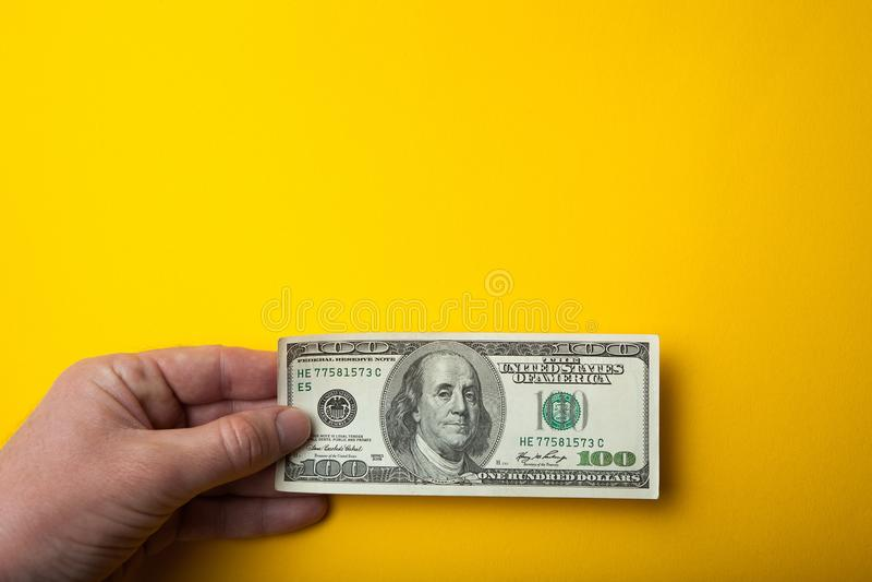 Handen rymmer 100 dollar på en gul bakgrund, tomt utrymme för text Begreppet av k?pande och att s?lja royaltyfria bilder