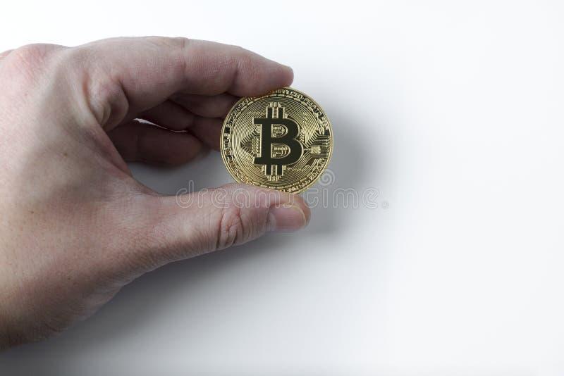 Handen rymmer en bitcoin på en vit bakgrund royaltyfria foton