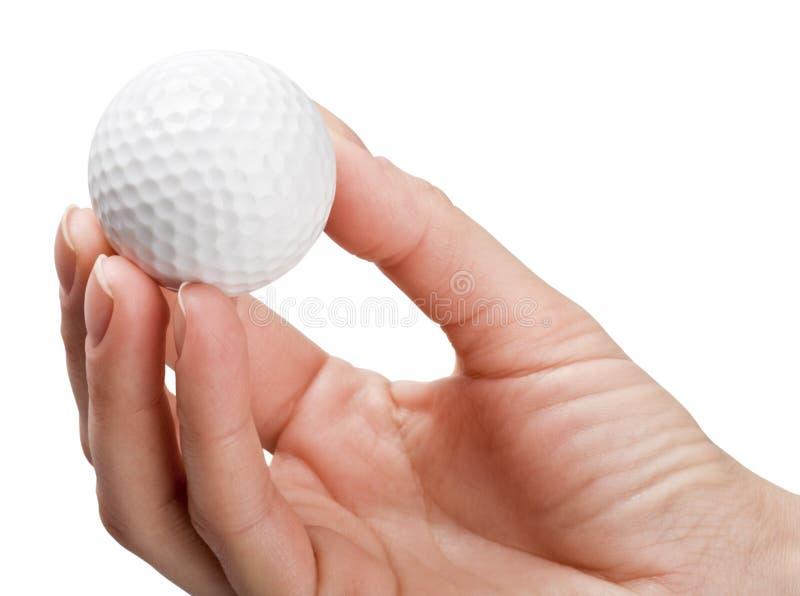Handen rymmer en boll för golf royaltyfria foton