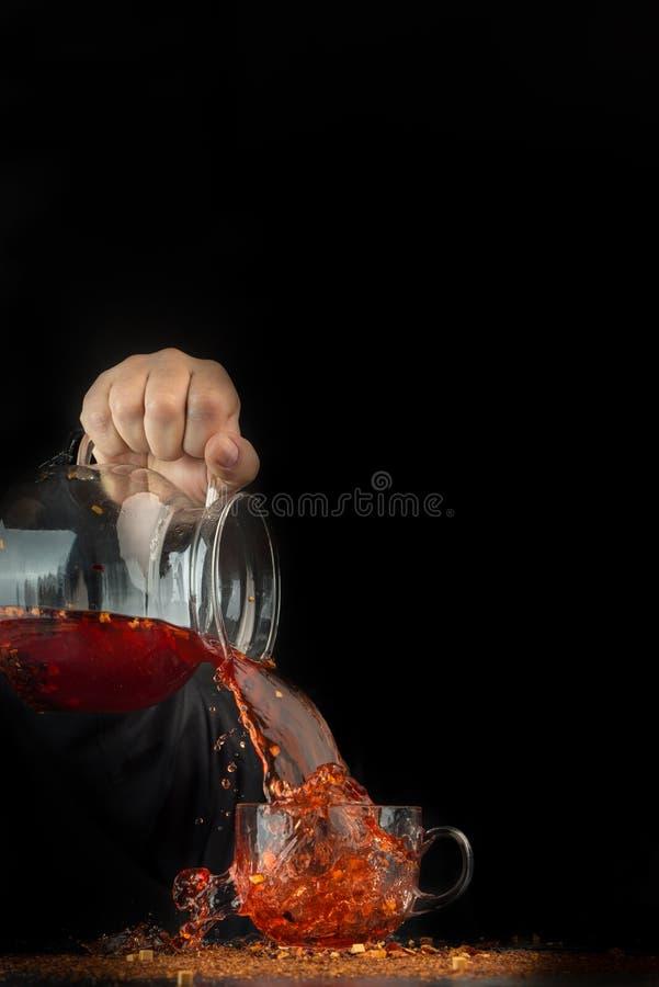 Handen rymmer en exponeringsglastillbringare i luften, ett fruktte häller från kannan med rörelseenergin som plaskar runt om kopp arkivbild