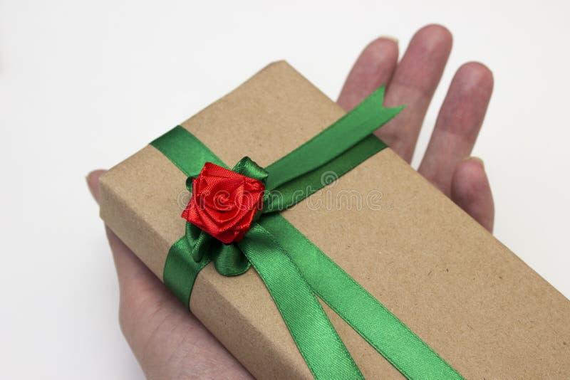 Handen rymmer en gåva för ferien som packas i pappers-, och bundet med ett grönt band med en röd blomma steg arkivbilder