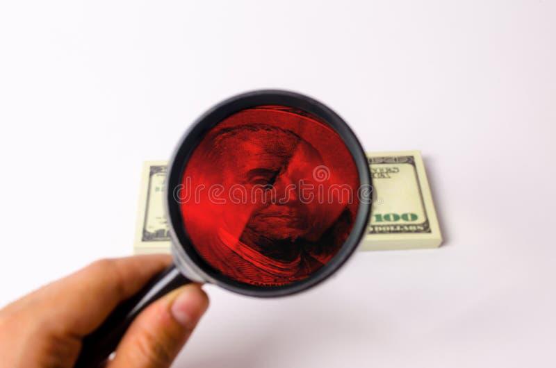 Handen rymmer ett förstoringsglas och ser en dollar royaltyfri foto