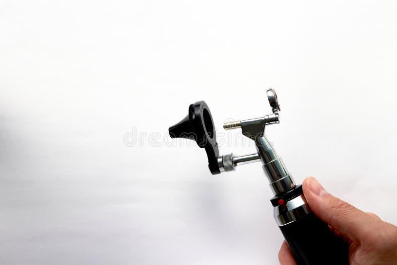 Handen rymmer otoscopen för ENT sikt för stycke för kotte för huvud för doktorsexamenöra på vit bakgrund fotografering för bildbyråer