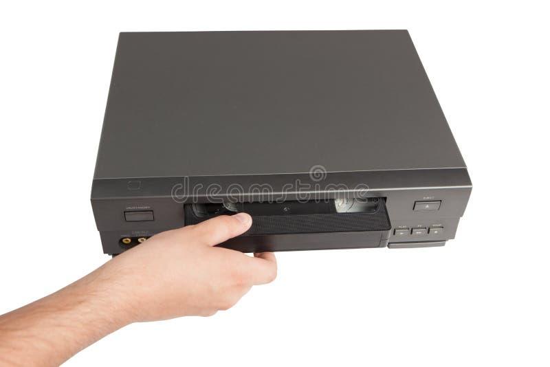 Handen sätter in videokassetten i videorecorder arkivbilder