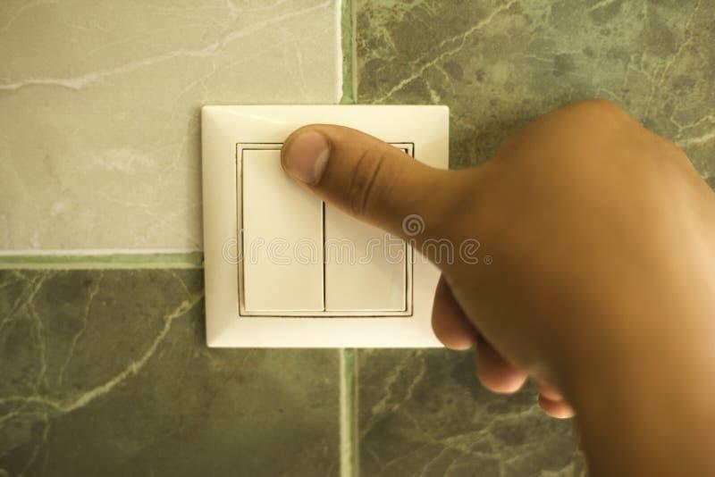 Handen sl?cker ljuset i badrummet genom att anv?nda en v?ggstr?mbrytare arkivbild