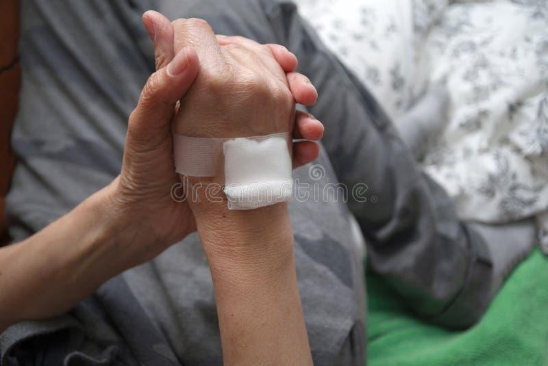 Handen som binds med vit, förbinder arkivfoton