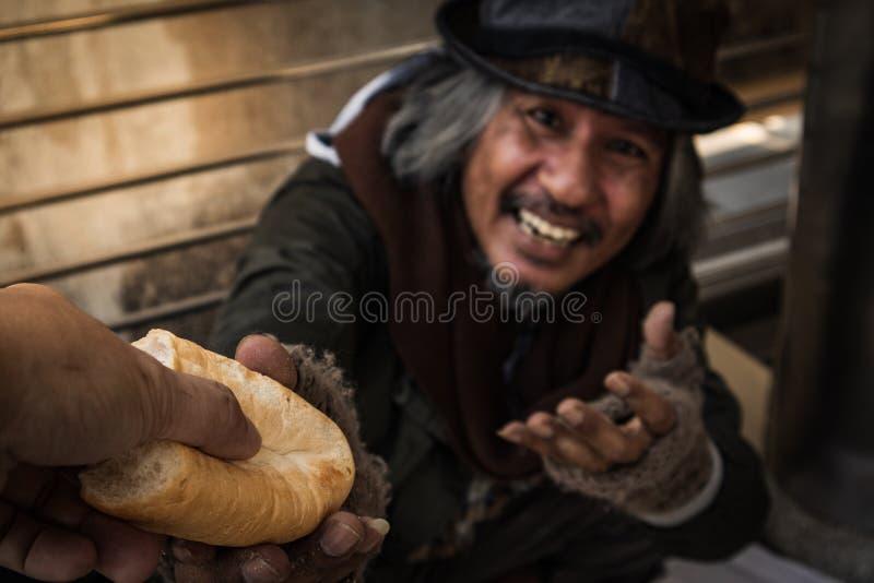 Handen som ger bröd, eller mat för att göra den hungriga hemlösa mannen har den lyckliga framsidan arkivfoton
