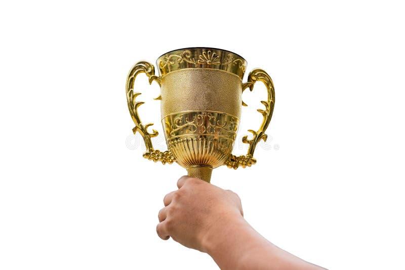 Handen som rymmer den guld- trofékoppen, lyfter upp på bakgrund royaltyfri fotografi