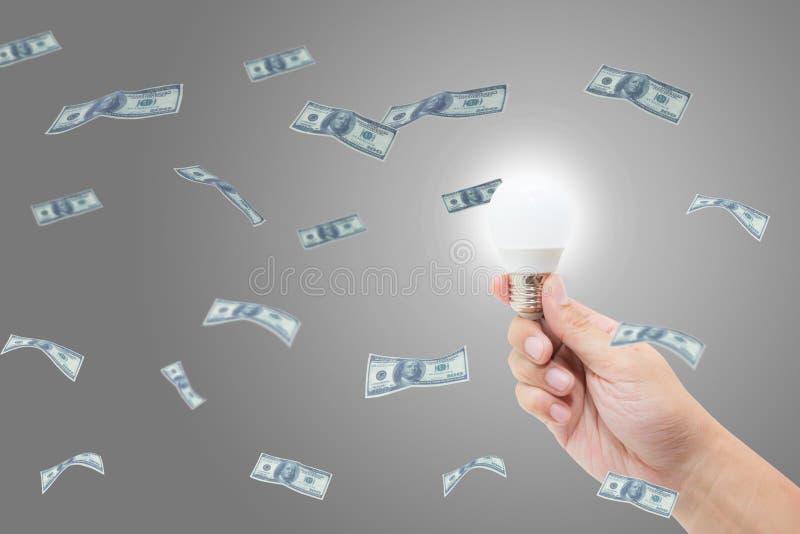 Handen som rymmer den ljusa ljusa kulan, har en framgångidé med pengardollaren arkivfoton