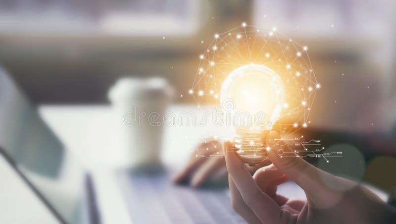 Handen som rymmer den ljusa kulan med innovativt, och kreativitet är tangenter till framgång Begreppskunskap leder till idéer och royaltyfria bilder