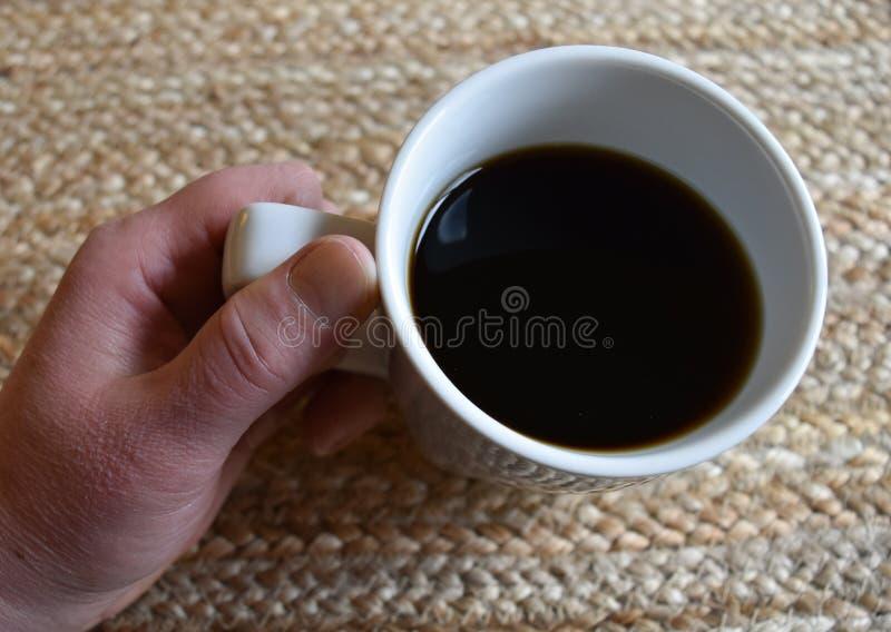 Handen som rymmer en vit kopp, fyllde med svart kaffe royaltyfri bild