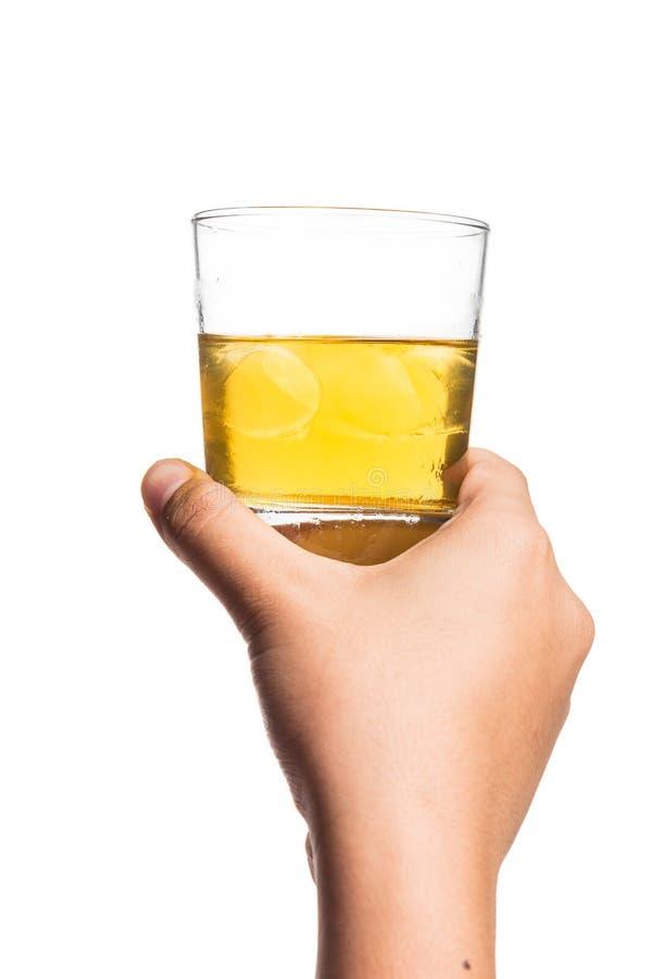 Handen som rymmer ett utspätt exponeringsglas av whisky på, vaggar royaltyfria bilder