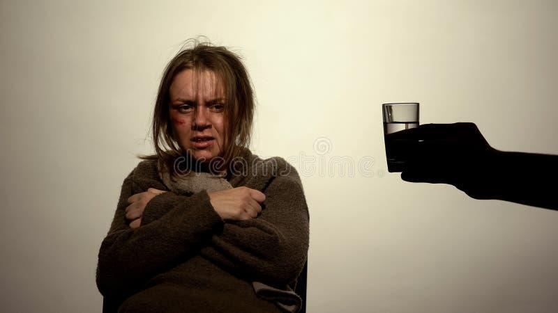 Handen som rymmer exponeringsglas av vodkaframdelen av alkohol, missbrukade kvinnligt, problemviljekraft royaltyfria bilder
