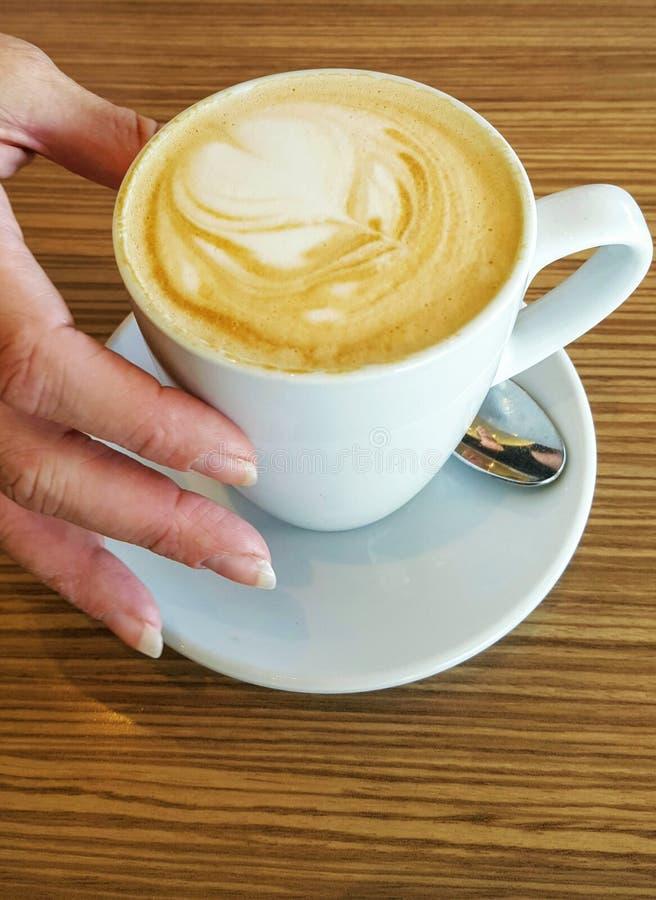Handen som rymmer vitt kaffe, rånar arkivbild