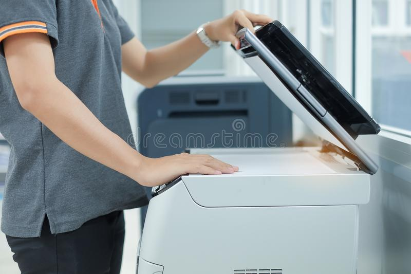 Handen som sätter ett dokumentpapper in i kopia för skrivarbildläsare eller laser-, bearbetar med maskin i regeringsställning royaltyfria bilder