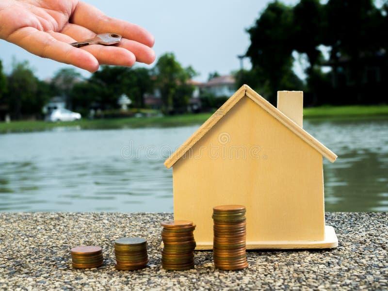 Handen som sätter pengarmynt, staplar att växa med huset bakom och att spara pengar för hem- begrepp arkivfoton
