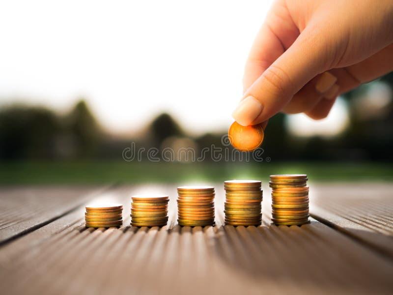 Handen som sätter pengarmynt, staplar att växa som sparar pengar för avsiktbegrepp arkivbilder