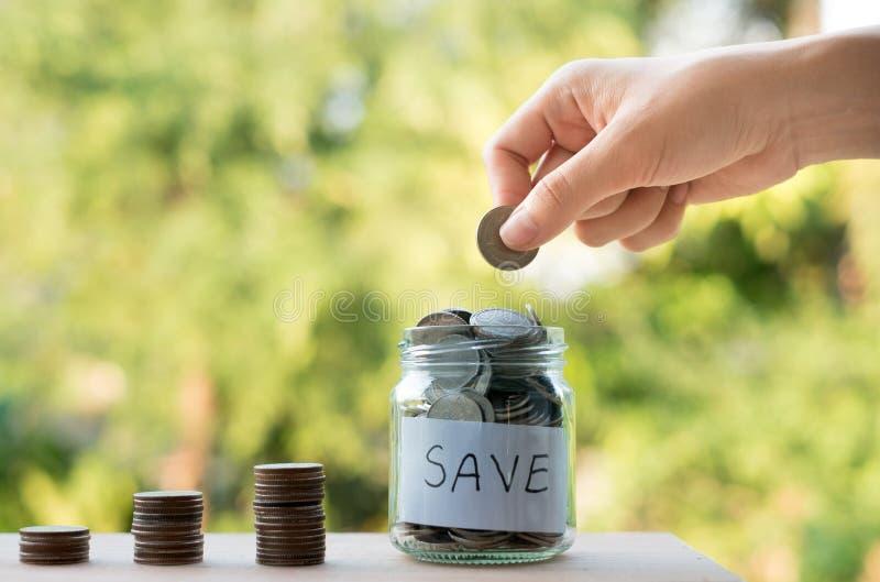 Handen som sätter pengarmynt, staplar att växa som sparar pengar för avsiktbegrepp arkivfoton