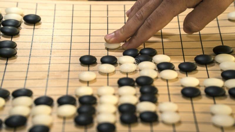 Handen som spelar svartvita stenstycken på kines, går eller Weiqi lekbrädet Inomhus aktivitet med konstgjort ljus fotografering för bildbyråer